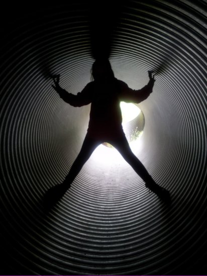 Person standing inside a pipe