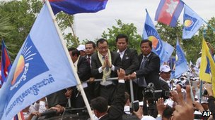 Sam Rainsy, centre, greets his supporters on arrival in Phnom Penh, Cambodia, on 19 July 2013