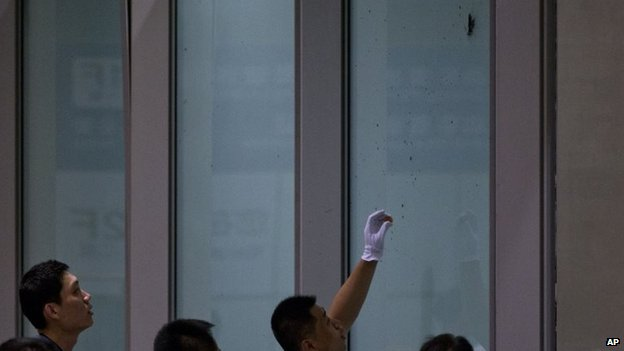 A policeman takes samples from explosive materials scattered on a glass wall.