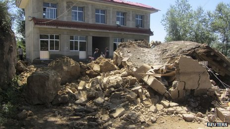 People stand next to a collapsed house after an earthquake struck Minxian county of Dingxi, Gansu province, 22 July 2013