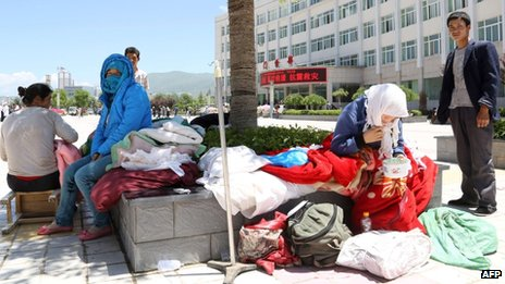 People wait outside the Minxian county hospital for treatment after an earthquake hit the area in Minxian county of Dingxi, northwest China's Gansu province on 22 July 2013