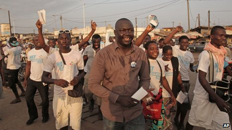 Gerry Taama (C) from the New Togolese Engagement party campaigns at a local market ahead of legislative elections in Lome, Togo