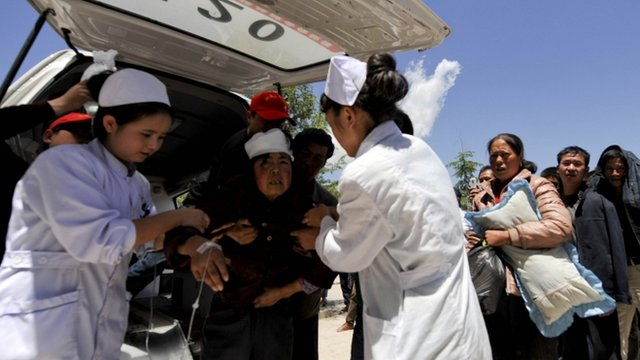 An injured woman is helped by medical workers