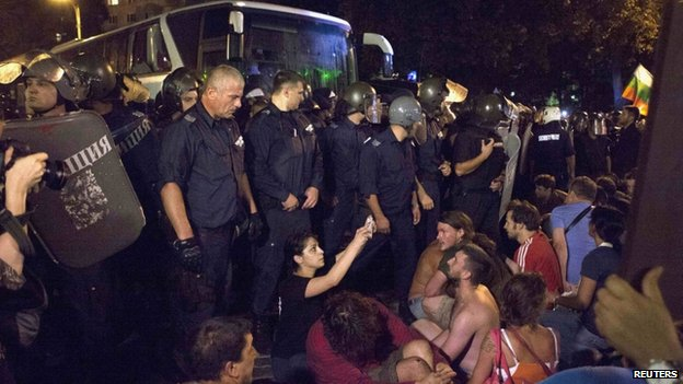 Protesters try to stop a heavily guarded bus trying to get deputies out of the parliament