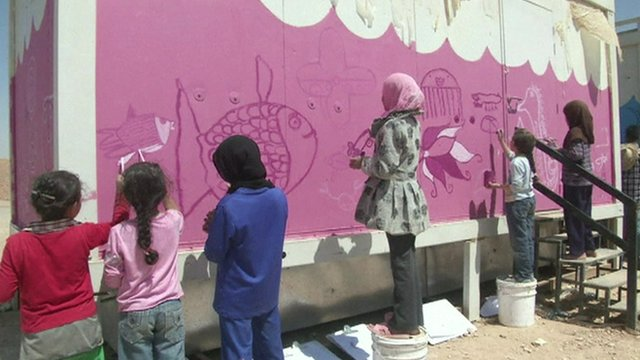Syrian refugee children paint a wall