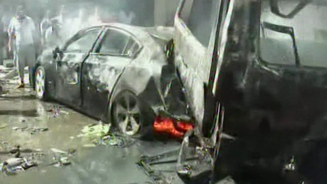 Burned-out remains of vehicles at scene of explosion