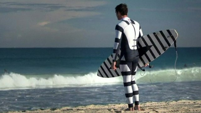 A surfer wearing a black and white striped wetsuit