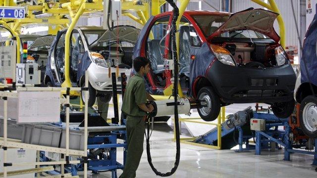 An employee works on a Tata Nano car