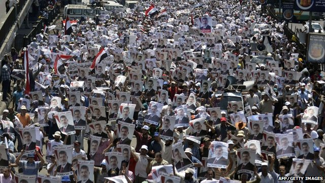 Supporters of the Muslim Brotherhood and Egypt's ousted president Mohamed Morsi carry his portrait as they demonstrate outside Rabaa al-Adawia mosque