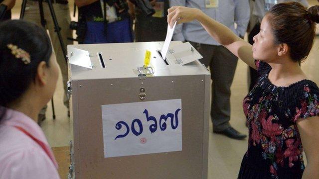 Woman putting voting paper into ballot box