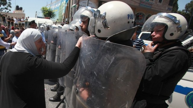 Palestinian woman and riot police