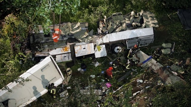 Firefighters work on the wreckage of the bus