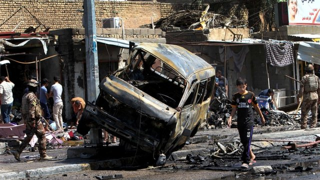 People and security forces inspect the site of a car bomb explosion in Basra