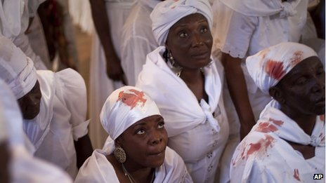 Women wearing clothes stained with blood from a sacrificed animal attend a Voodoo ceremony in Souvenance, Haiti, on 24 April, 2011.