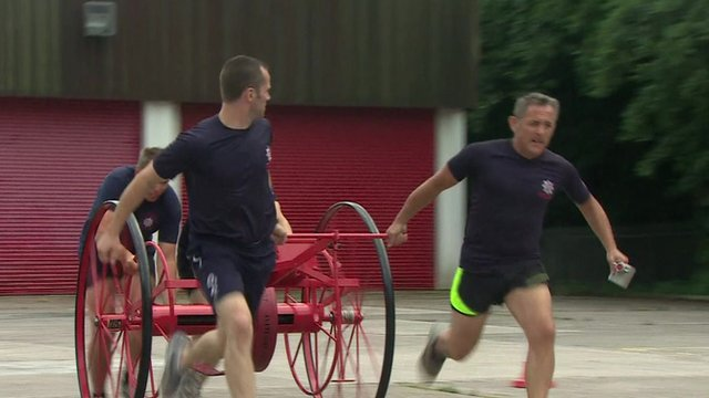 Firefighters pulling large hose on wheels