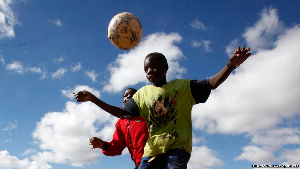 Children challenge each other as they play football in Mbare outside of Harare