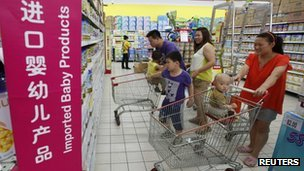A family looks at foreign imported milk powder products at a supermarket in Beijing July 3, 2013.