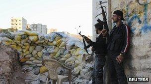 Free Syrian Army fighters take cover near sandbags in Ashrafieh, Aleppo, 5 August 2013