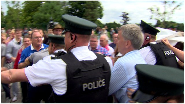 Police escort Lord Mayor of Belfast, Máirtín Ó Muilleoir, through the Woodvale area of the city