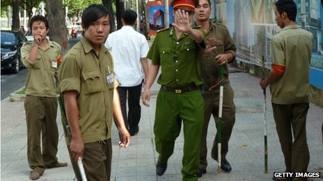 Vietnamese police and local militia try to stop a photographer taking pictures