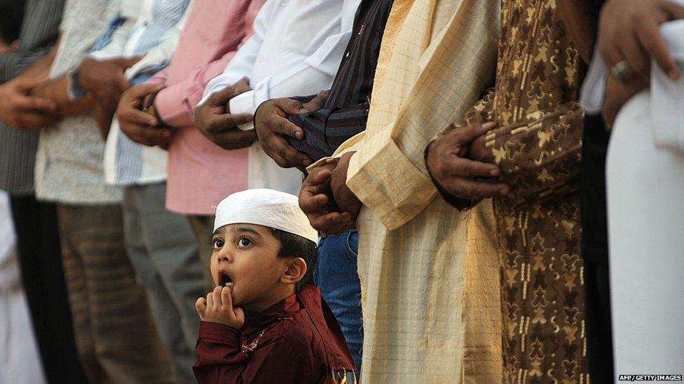 A Saudi young boy looks up during the morning Eid al-Fitr prayer at Turki bin Abdullah grand mosque in Riyadh, Saudi Arabia (8 August 2013)