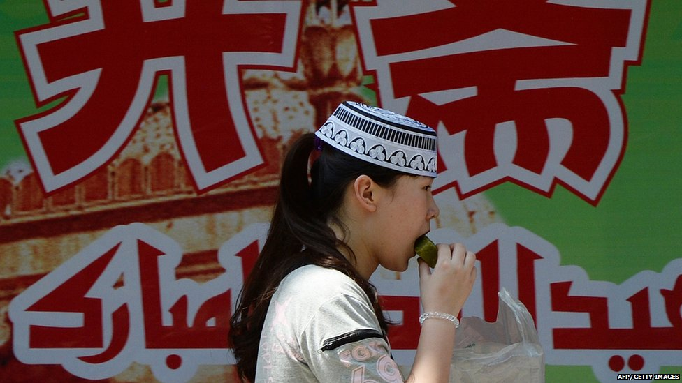 Chinese Hui Muslim girl eats a festive snack as she celebrates the end of fasting near the historic Niujie Mosque in Beijing (8 August 2013)
