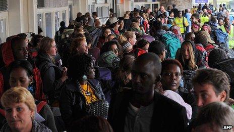 Air travellers queue as they wait to board their flights at Jomo Kenyatta International Airport in Nairobi on 8 August 2013