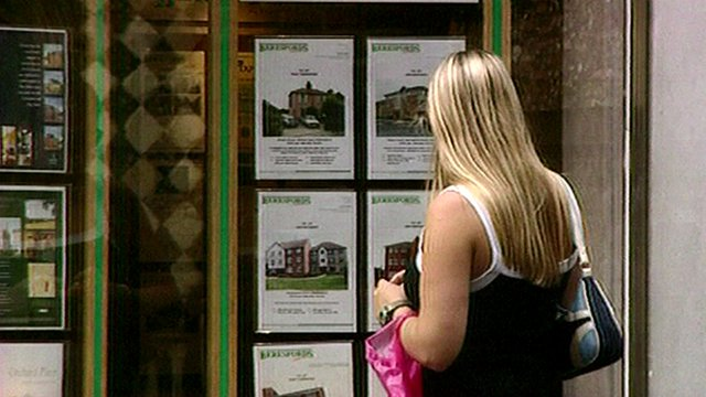 Woman looking at estate agent window