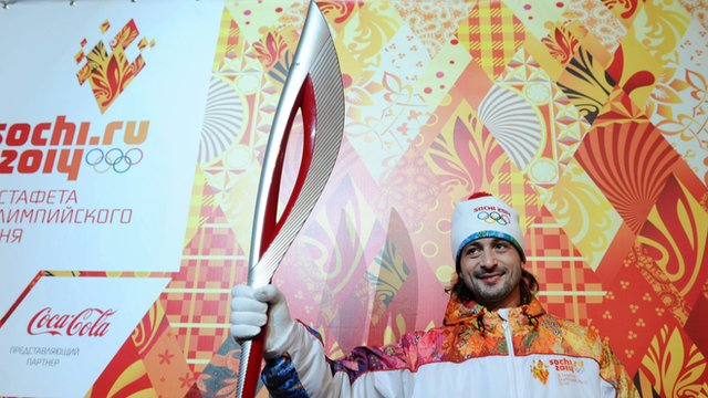 Russian ice dancer Ilia Averbukh poses with a Sochi 2014 Olympic Torch