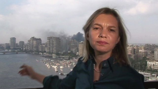 BBC Correspondent Bethany Bell points to black plumes of smoke in Egypt's capital of Cairo