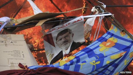 A poster among flames as riot police clear supporters of deposed Egyptian President Mohammed Morsi from a camp at Rabaa al-Adawiya square in Cairo on 14 August 2013