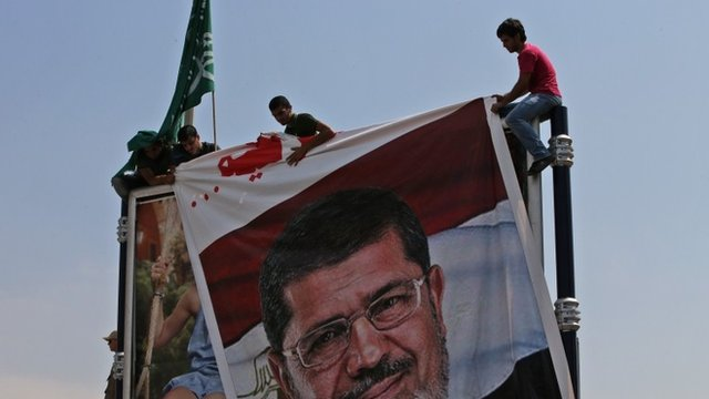 Lebanese supporters of the Islamic Group, a Lebanese faction linked to the Muslim Brotherhood, install a big portrait of ousted Islamist President Mohammed Morsi at a street advertising board during a protest at the Egyptian Embassy in Beirut, Lebanon