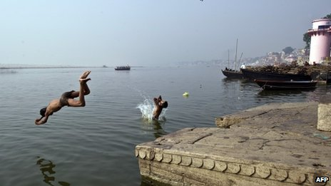 Indian boys jump in Ganges river in Varanasi on April 26, 2013. Varanasi, is a city on the banks of the Ganges in Uttar Pradesh