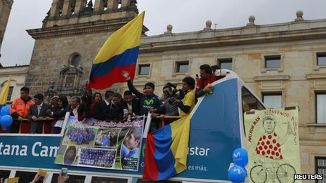 Nairo Quintana waves from an open top bus in Bogota on 13 August 2013