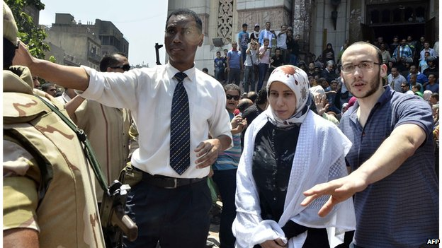 Egyptian army officer (L) helps an Islamist woman to leave Cairo's Al-Fath mosque (17 August 2013)