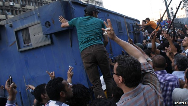Supporters of the interim government installed by the army gather around a police van carrying Muslim Brotherhood supporters from the al-Fath mosque (17 August 2013)