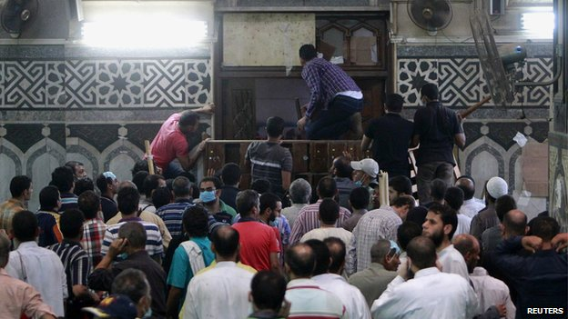 Demonstrators in support of ousted Egyptian President Mohammed Morsi wait by the barricaded door inside al-Fath mosque at Ramses Square in Cairo (17 August 2013)