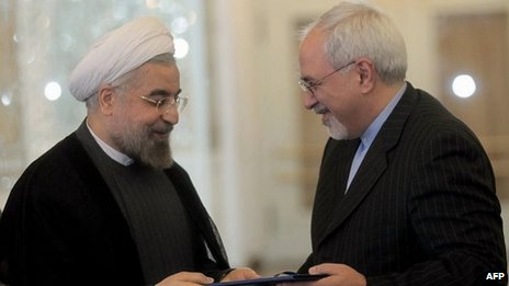 A handout picture released by the Iranian president's official website shows Iranian President Hassan Rouhani (L) handing over a decree to newly appointed Foreign Minister Mohammad Javad Zarif (R), during a ceremony at the foreign ministry in Tehran on Saturday