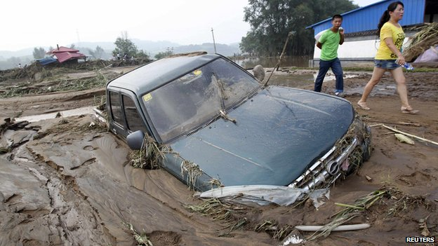People walk past a car stranded in mud after heavy rainfalls hit Fushun, Liaoning province (17 August 2013)