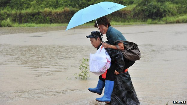 A rescue worker carries a woman out of a flooded area in Daoxian county, Hunan province, August 18, 2013