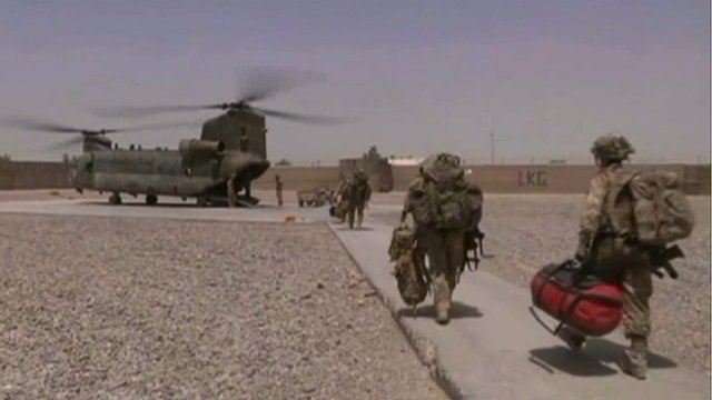 British troops carry bags to an Apache helicopter