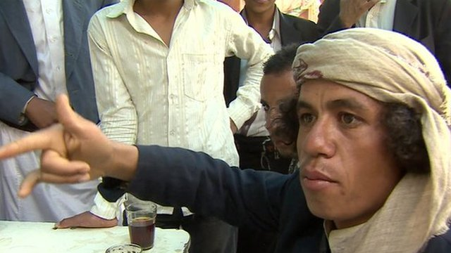 A Yemeni man, amongst a group of men - discussing how US bombing has affected their lives