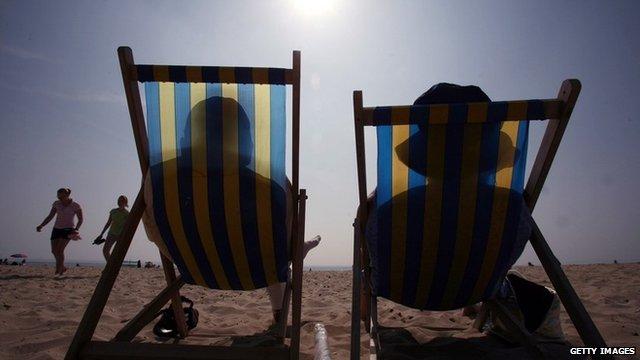 Two people sunbathing on deck chairs