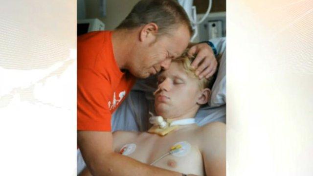 Mark Smith hugs his son, who lies in a coma