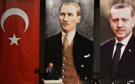 Erdogan gestures as he gives a speech under a Turkish flag and portraits of himself and Ataturk