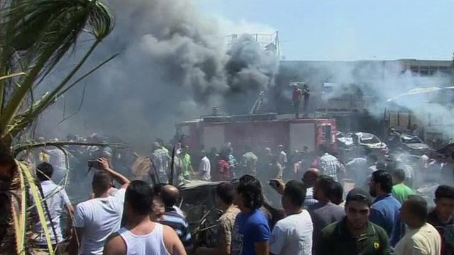 Smoke and emergency vehicles in Tripoli in the aftermath of the blasts