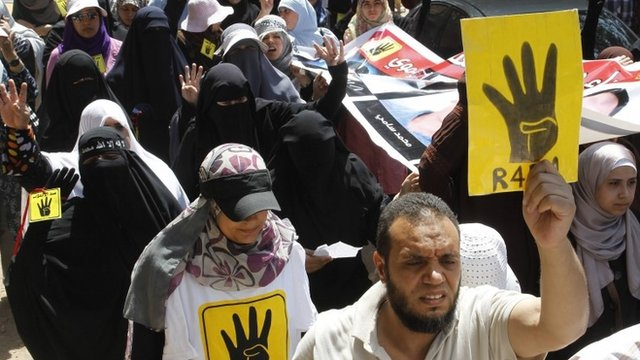 Supporters of Muslim brotherhood hold up posters showing 'Rabaa' gesture