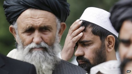 An Afghan villager holds his head as he listens with other Afghan villagers at a news conference following a sentencing hearing for Staff Sgt Robert Bales at Joint Base Lewis-McChord, Washington state, on 23 August 2013