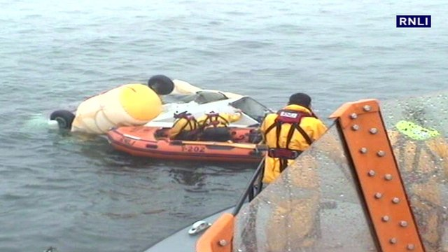 RNLI crew with wreckage of crashed helicopter