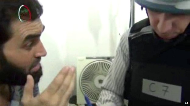 Image taken from amateur video footage, a UN inspector, right, speaks to a man about the alleged chemical weapon attack at a makeshift hospital in Muadhamiya, Damascus, on 26 August 2013